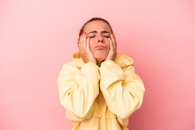 Giovane donna russa isolata su sfondo rosa piagnucolando e piangendo sconsolatamente.