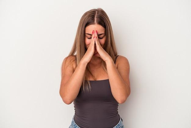 La giovane donna russa isolata su fondo bianco che tiene le mani in preghiera vicino alla bocca, si sente sicura.