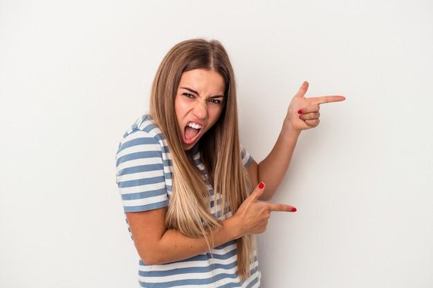 La giovane donna russa isolata su fondo bianco tiene lo spazio della copia su una palma, tiene la mano sulla guancia. stupito e deliziato.