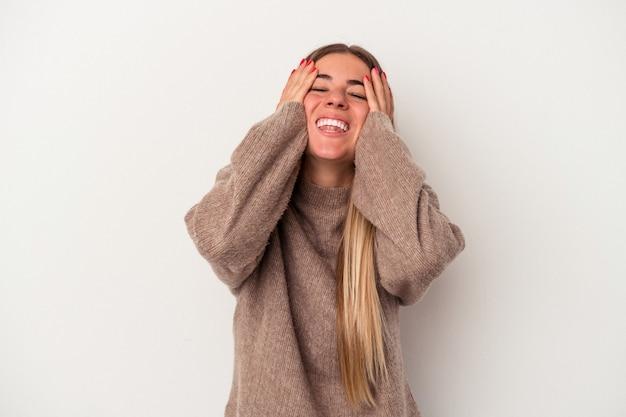 La giovane donna russa isolata su fondo bianco alza le spalle e apre gli occhi confusi.