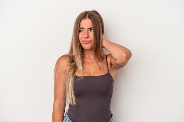 Giovane donna russa isolata su sfondo bianco toccando la parte posteriore della testa, pensando e facendo una scelta.