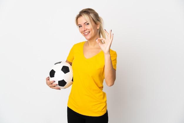 Giovane donna russa isolata su sfondo bianco con pallone da calcio e facendo segno ok