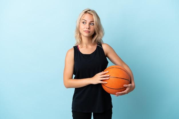 Giovane donna russa che gioca a basket isolato su sfondo blu che fa il gesto di dubbi cercando di lato