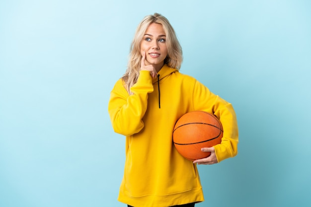 Giovane donna russa che gioca a basket isolato su sfondo blu pensando un'idea mentre guarda in alto