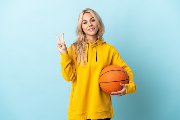 Giovane donna russa che gioca a basket isolato su blu sorridente e mostrando il segno di vittoria