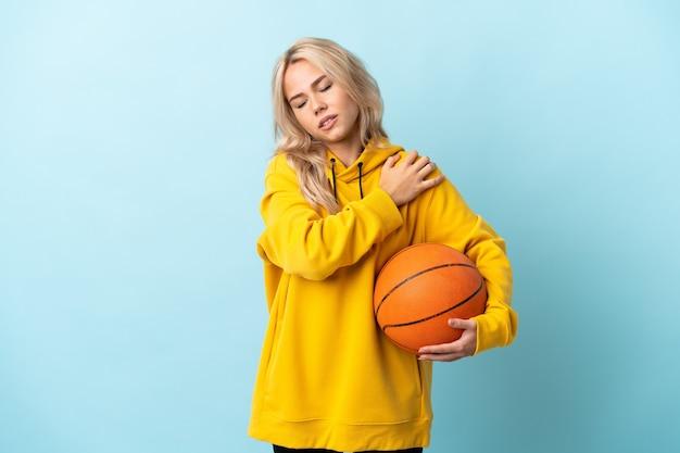 Giovane donna russa che gioca a basket isolato su blu che soffre di dolore alla spalla per aver fatto uno sforzo