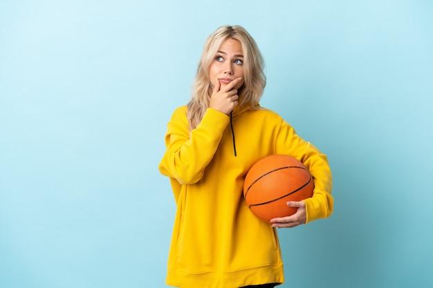 Giovane donna russa che gioca a basket isolato sulla parete blu avendo dubbi e con confondere l'espressione del viso