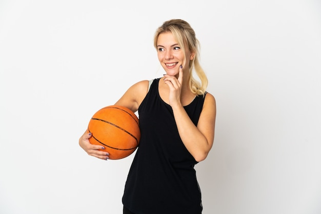 Giovane donna russa che gioca a basket isolato su sfondo bianco pensando un'idea mentre osservava