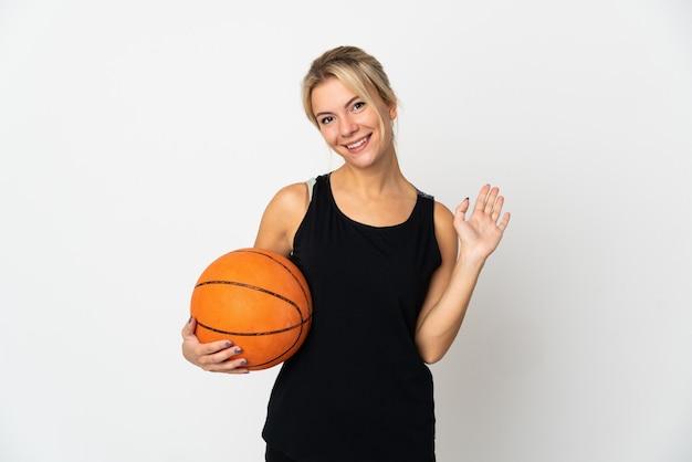 Giovane donna russa che gioca a basket isolato sul muro bianco salutando con la mano con l'espressione felice