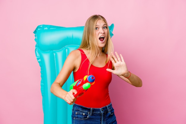 Giovane donna russa che gioca con una pistola ad acqua con un materasso ad aria scioccata a causa di un pericolo imminente