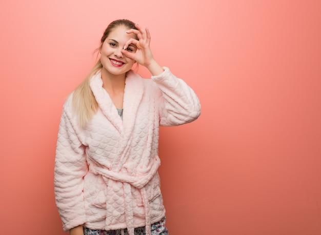 Giovane donna russa che indossa il pigiama fiducioso facendo il gesto giusto sull'occhio