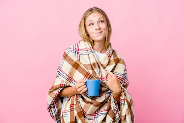Giovane donna russa avvolta in una coperta che beve caffè sognando di raggiungere obiettivi e scopi