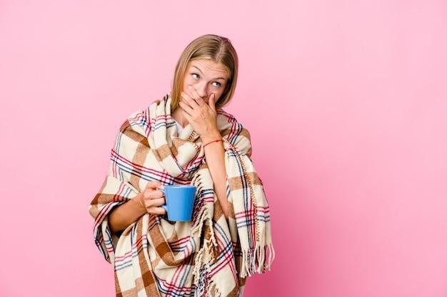 Giovane donna russa avvolta in una coperta che beve caffè premuroso alla ricerca di uno spazio di copia che copre la bocca con la mano.