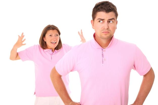 Un giovane uomo triste in piedi su bianco e sua moglie che grida nel retro