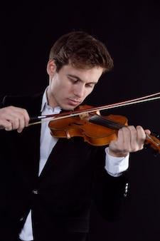 Un giovane violinista triste suona un assolo in un'orchestra sinfonica