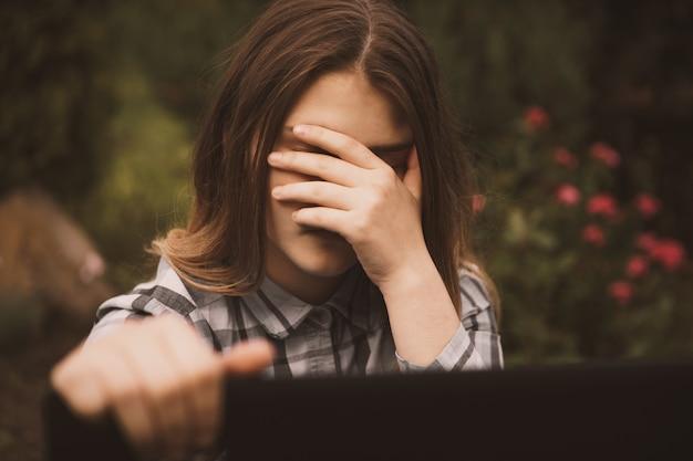 Giovane ragazza triste e vulnerabile che utilizza il telefono cellulare spaventata e disperata che soffre di abusi online cyberbullismo perseguitato e molestato nel concetto di cyber bullismo adolescente