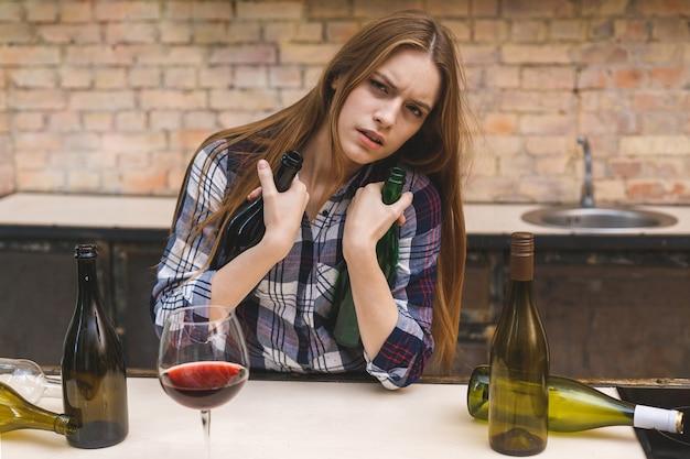 Giovane donna alcolica triste e sprecata che si siede al divano della cucina a bere vino rosso, completamente ubriaco cercando depresso solitario e sofferenza postumi di una sbornia in alcolismo e abuso di alcol.