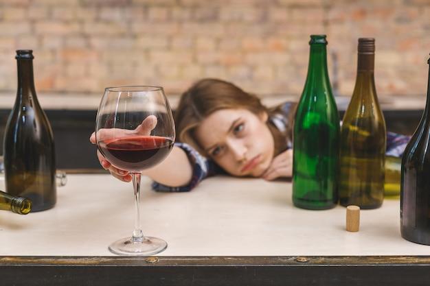 Giovane donna alcolica triste e sprecata che si siede allo strato della cucina che beve vino rosso che giudica di vetro completamente ubriaco alla ricerca di postumi di una sbornia solitari e di sofferenza depressi nell'alcolismo e nell'abuso di alcool.