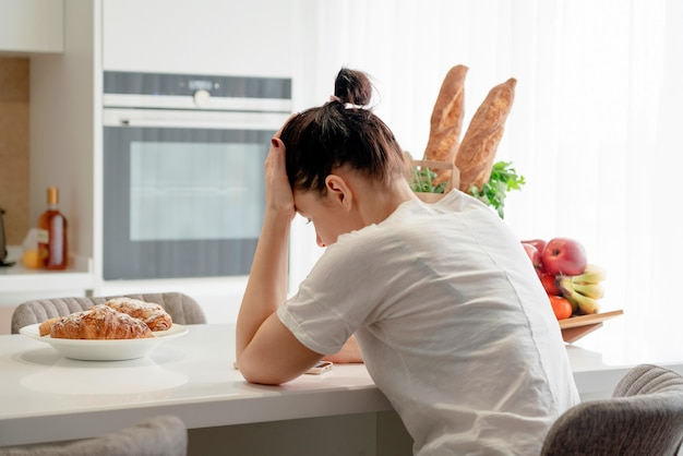Giovane donna triste che soffre in cucina, casalinga sollecitata in cucina