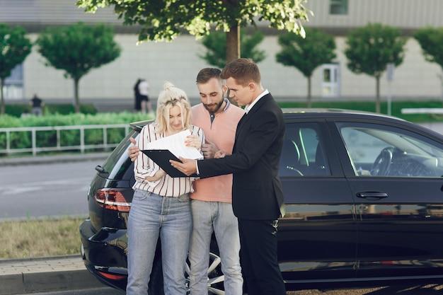 Un giovane venditore mostra ai clienti un'auto nuova. coppia, uomo e donna felici acquistano una nuova auto. i giovani firmano documenti per acquistare un'auto.