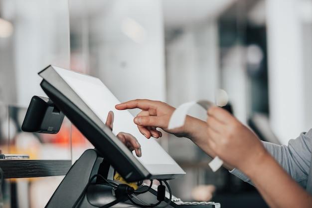 Giovane commessa che esegue il pagamento del processo sul pos touchscreen, contando la vendita nel registratore di cassa, concetto finanziario finance