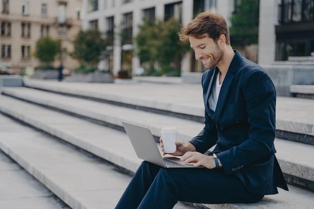 Giovane uomo d'affari soddisfatto in abito elegante seduto sulle scale fuori con laptop e caffè per andare