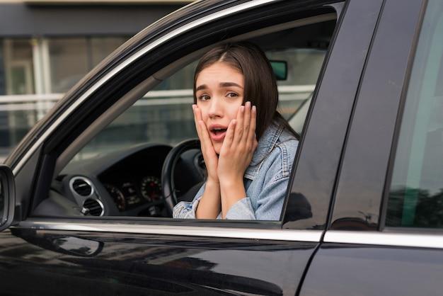 La giovane bella donna spaventata è in macchina