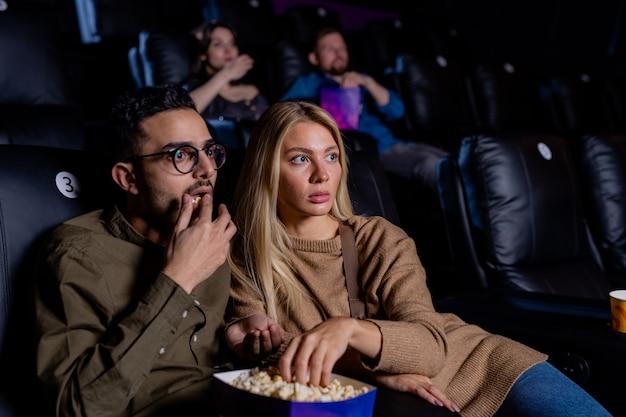 Giovani appuntamenti spaventati con scatola di popcorn seduti nel cinema buio e guardando film horror a piacimento