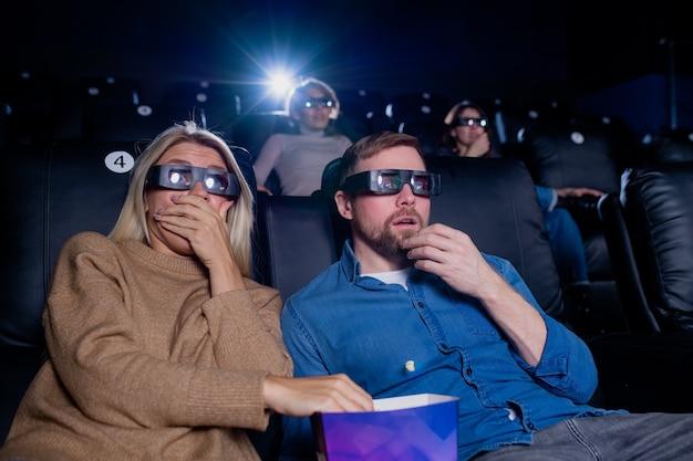Giovane uomo spaventato e donna occhiali 3d con popcorn mentre si guarda un film horror o d'azione su grande schermo