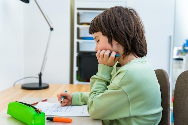 Giovane ragazzo della scuola che fa il suo lavoro seduto al tavolo a casa. bambino concentrato pensando a un compito. istruzione homeschooliong.