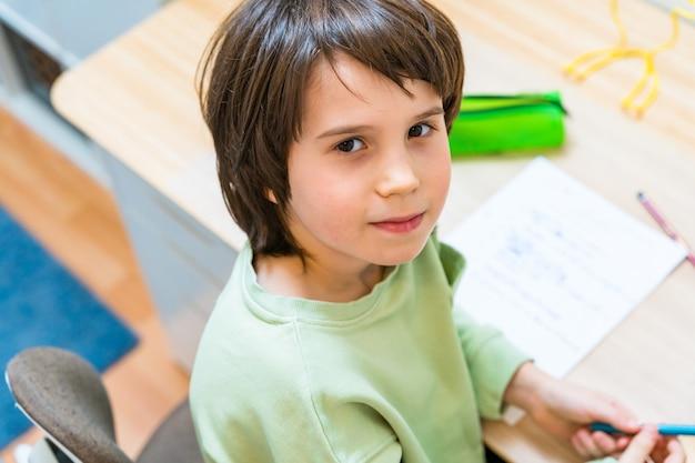 Giovane ragazzo della scuola che fa il suo lavoro seduto al tavolo a casa. bambino concentrato esercizi di scrittura con piacere. concetto homeschooliong.