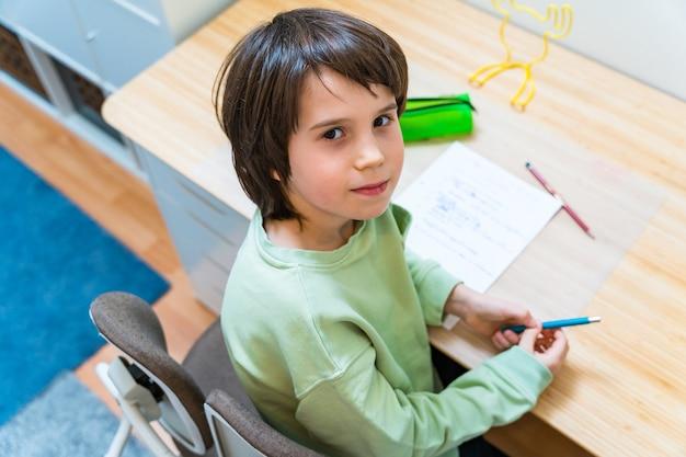Giovane ragazzo della scuola che fa il suo lavoro seduto al tavolo a casa. bambino concentrato esercizi di scrittura con piacere. istruzione homeschooliong.
