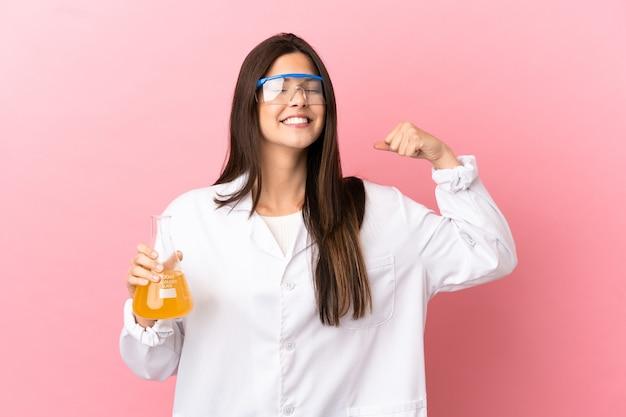 Giovane ragazza scientifica su sfondo rosa isolato facendo un forte gesto