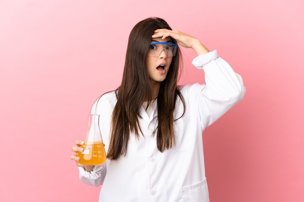 Giovane ragazza scientifica su sfondo rosa isolato facendo gesto di sorpresa mentre guarda al lato