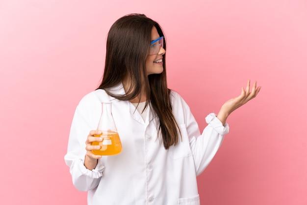 Giovane ragazza scientifica su sfondo rosa isolato che estende le mani a lato per invitare a venire