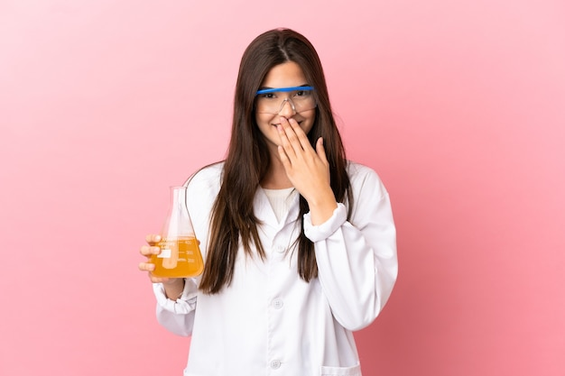 Giovane ragazza scientifica su sfondo rosa isolato felice e sorridente che copre la bocca con la mano