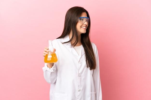 Giovane ragazza scientifica su sfondo rosa isolato guardando il lato