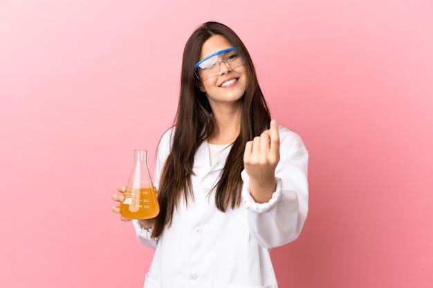 Giovane ragazza scientifica su sfondo rosa isolato che fa il gesto dei soldi