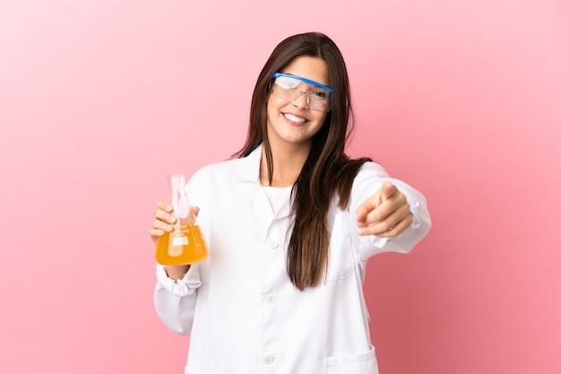 Giovane ragazza scientifica su sfondo rosa isolato che punta davanti con felice espressione