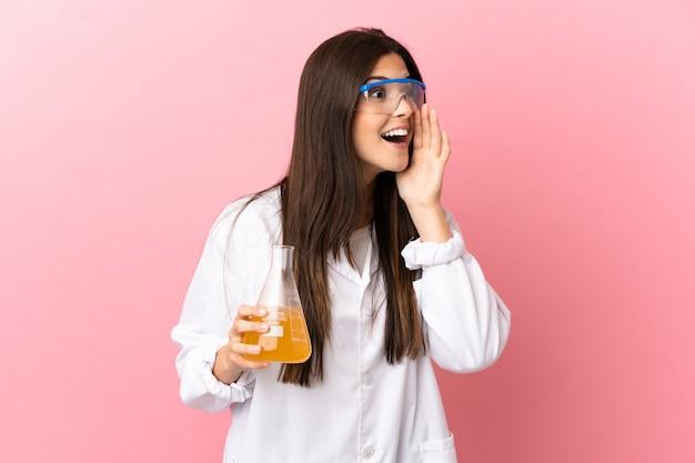 Giovane ragazza scientifica su sfondo rosa isolato che grida con la bocca spalancata di lato