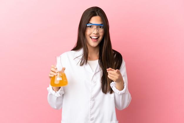 Giovane ragazza scientifica su sfondo rosa isolato sorpreso e rivolto verso la parte anteriore