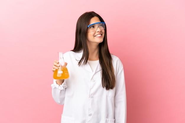 Giovane ragazza scientifica sopra fondo rosa isolato che pensa un'idea mentre osserva in su