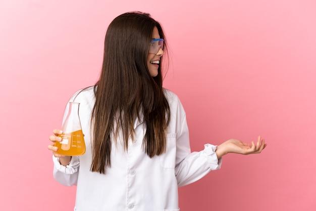 Giovane ragazza scientifica su sfondo rosa isolato con espressione di sorpresa mentre guarda il lato
