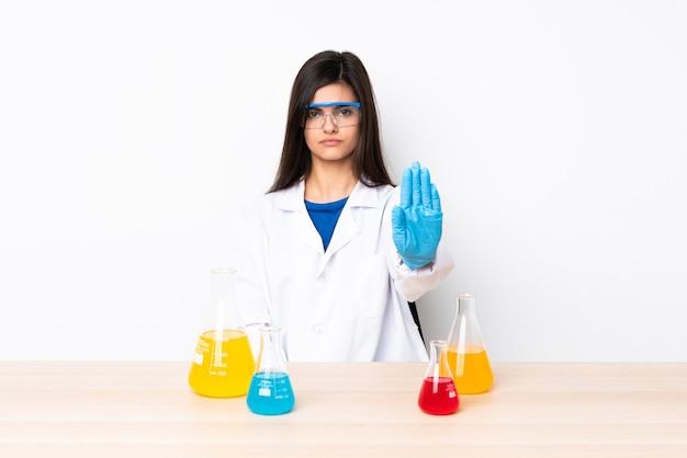 Giovane donna scientifica in una tabella che fa gesto di arresto