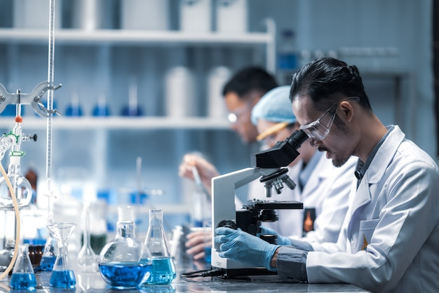 Giovane scienziato che osserva tramite un microscopio in un laboratorio. giovane scienziato che fa delle ricerche.