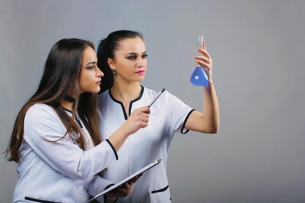 Giovani scienziati in possesso di pallone con reagenti e fare test o ricerche scientifiche in laboratorio. chimica e concetto di persone.