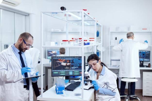Giovani scienziati con tablet pc e microscopio che fanno test in un laboratorio occupato. team di ricercatori che fanno ingegneria farmacologica in un laboratorio sterile per l'industria sanitaria con assistente africano nel