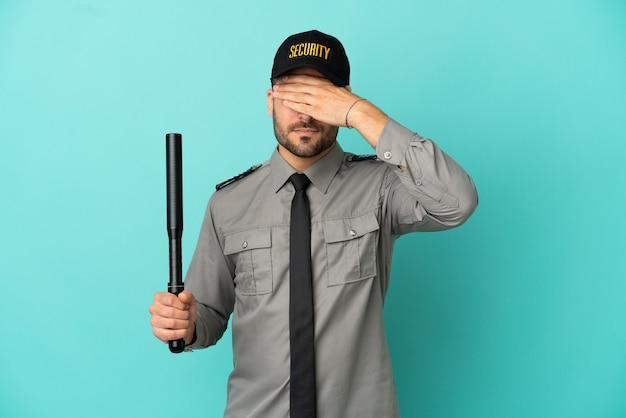 Giovane uomo della sicurezza isolato su sfondo blu che copre gli occhi con le mani. non voglio vedere qualcosa