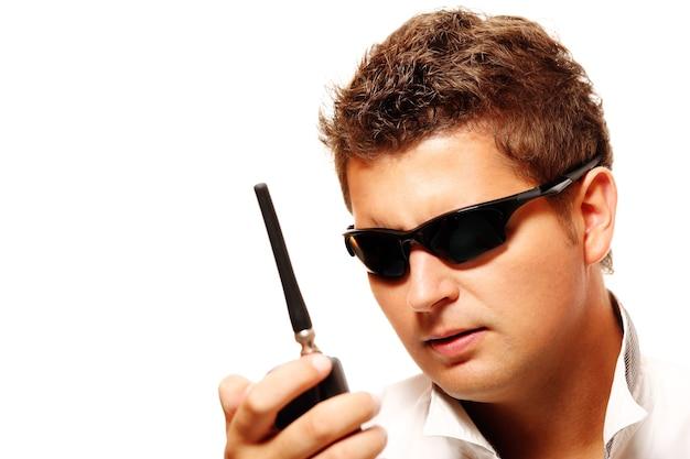 Giovane uomo della sicurezza con trasmettitore radio su sfondo bianco