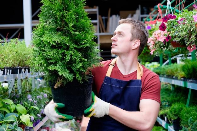 Giovane venditore nel mercato delle piante